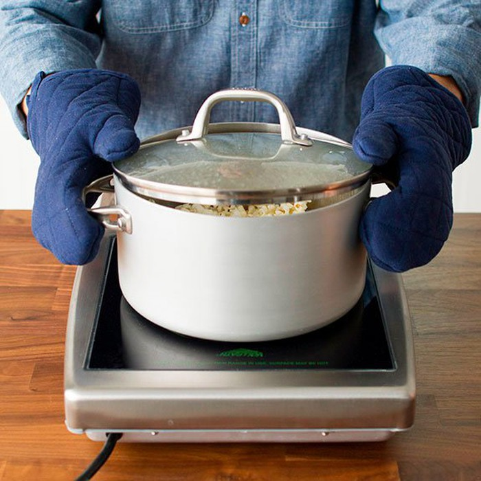 Cần quai nồi lắc mạnh để hạt bắp được đều và nổ bung ra - cách rang bắp rang bơ