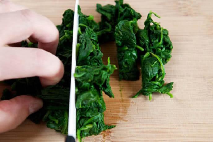 Vắt nhẹ rau cải bó xôi đã chần để loại bỏ bớt nước rồi thái thành từ khúc vừa ăn