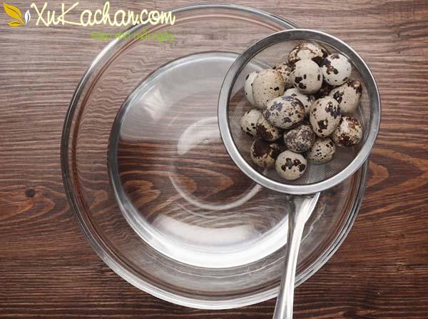 Trứng cút sau khi luộc vớt ra, ngâm vào bát nước lạnh để bóc dễ dàng hơn